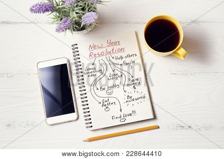 New Year Resolution In Notebook On White Wooden Desk