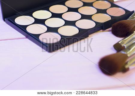A Palette Of Concealer And Foundation And A Set Of Brushes On White Wooden Background, Close Up