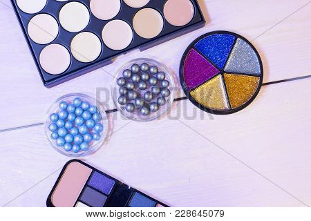 A Palette Of Concealer And Foundation, Grey And Blue Pearl Eyeshadow In Balls And A Box Of Colorful