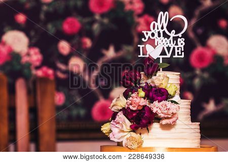 Three-tiered Wedding Cake Decorated With Beautiful Flowers And Wooden Inscription