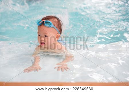 Cute Little Asian 18 Months / 1 Year Old Toddler Boy Child In Trunks Wear Swimming Goggles Learn To