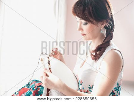 Young Beautiful Woman Is Engaged In Embroidering A Dagger On The Embroidery Frame In A Colored Dress