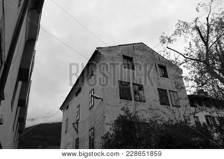 Old Abandoned House With Cracked Walls In Black And White. Damaged Ancient Building With Shut And Br