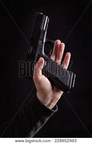 Hand Holding A Semi Automatic Handgun (glock) On A Black Background
