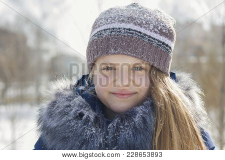 Portrait Of Teen Girl In Cap And Jacket With Fur Collar In Winter Covered By Snow, Youth Fashion