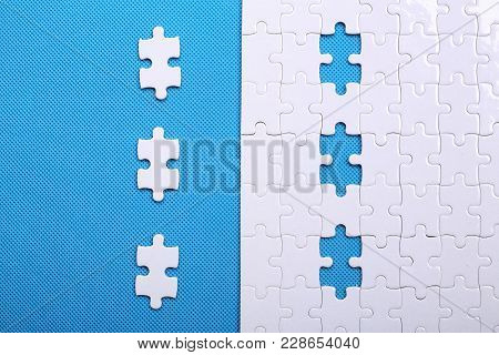 White Details Of A Puzzle On Blue Background. A Puzzle Is A Puzzle From Small Pieces. Heart Shape Of