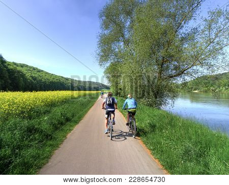 Two People Cycling On A Rural Road In Spring Alongside A Crop Of Colorful Yellow Rapeseed And A Tran