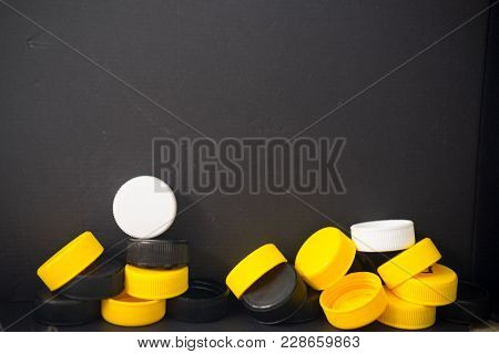 Plastic Caps From Bottles (black And Yellow) On Black Background