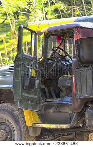 In The Cabin Of A Military Truck, A Dashboard And A Steering Wheel With Pedals