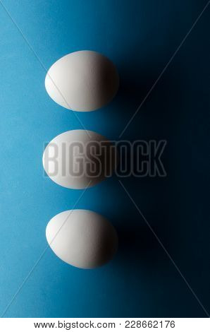 Three White Chicken Eggs On Black And Blue Background. The Concept Is Black And White Stripe.vertica