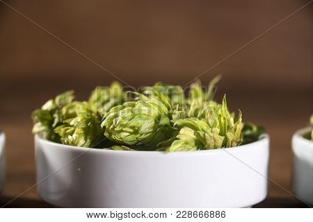 Beer Brewing Ingredients Hop Cones In White Bowl On Wooden Background. Beer Brewery Concept.