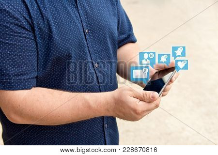 Young Man Holding Smartphone With Icons Of Notifications From Social Media. Social Media Concept. Ch