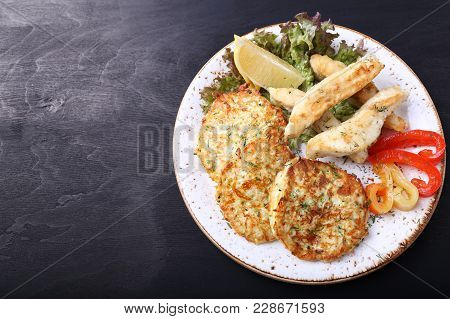 Fried Fish With Zuccini Pancakes And Fresh Vegetables. Top View