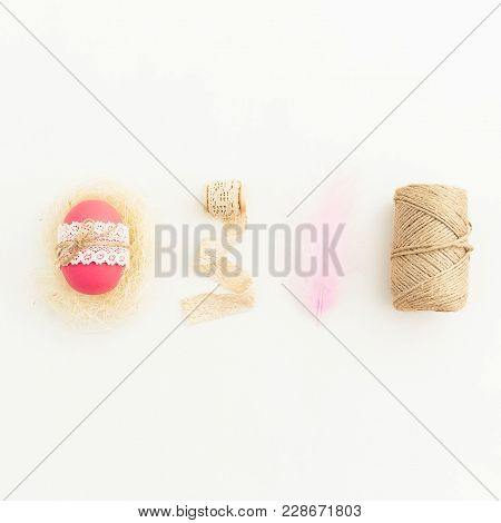 Easter Composition With Pink Eggs With Twine, Feather And Tapes On White Background, Top View, Fat L