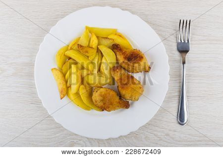 Fried Chicken Winglets In Breading, Potato In Plate, Fork On Wooden Table. Top View