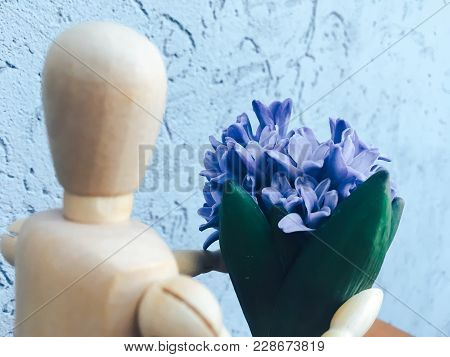 Wooden Faceless Man Gives Blue Flowers One