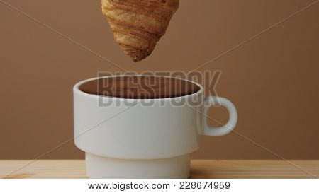 Closeup Of Croissant Immerse Into Hot Chocolate In Cup. Hot Chocolate Take Out Of Cup Making Smuges