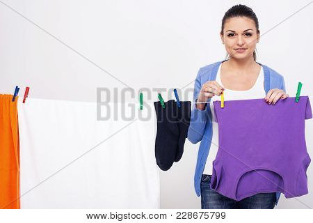 Young Woman Is Hanging Clothing On Clothesline On White Background.