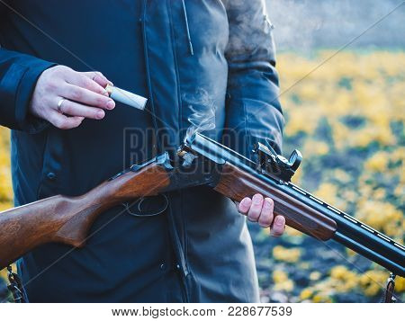 Sports Shooting. Hunter Reloading Cartridge In Field. Smoke From The Trunks Of Smooth-bore Hunting R