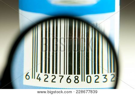 Scratched Paper Bar Code On Used Product Through Magnifying Glass Close Up Macro Shot On Blue Tone .