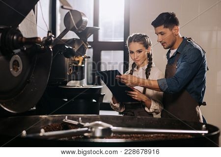 Coffee Shop Workers Checking Coffee Beans Roasting Process Together