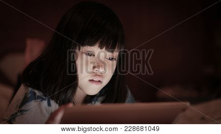 Cute Asian Kid Girl Using Tablet, In Darkness Room At Home, Bright Screen Light Reflex On Her Face.