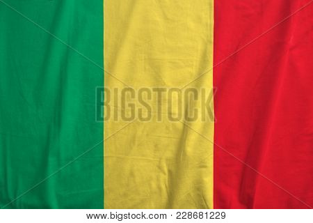 Malian Flag Blowing In The Wind. Fabric Texture Of The Flag Of Mali.