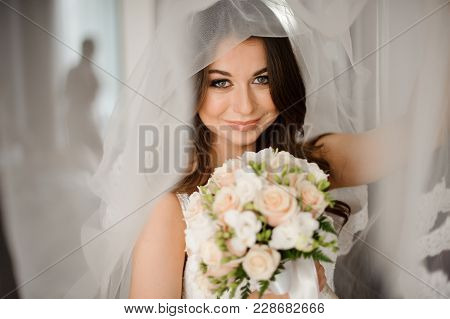 Bride Morning Preparation. Beautiful Bride In White Wedding Negligee And Veil On The Background Of L