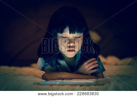 Asian Kid Girl Using Tablet Watching Movie While Lying On Bed, In Dark Background Of Bedroom, Bright