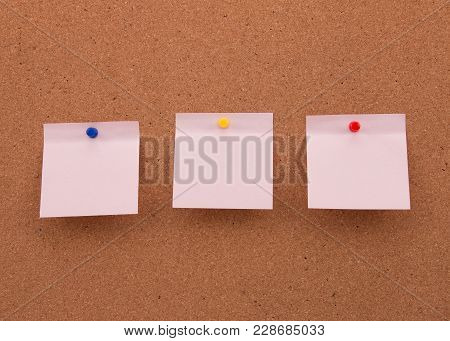 Three Stickers On The Board Pinned With Colored Studs