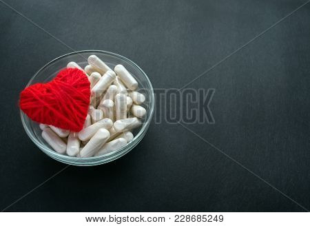 White Veg Capsules And Red Thread Heart In Glass Bowl On Black Background. Anticoagulant, Blood Thin