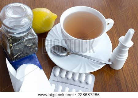 A Cup Of Tea With Saucer And Spoon, Lemon, Medicines, A Glass Dose With Tea, Paper Handkerchiefs, Na