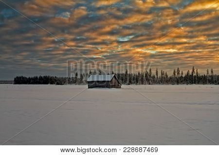 A Small Barn House Stands On The Snowy Fields Under A Dramatic Sunset. The Forest In The Background