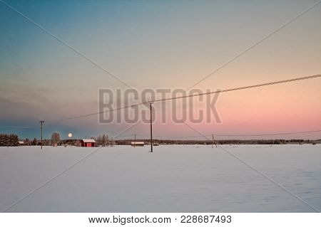 The Sun Rises Over The Rural Scenery At The Northern Finland. You Can Still See The Setting Full Moo
