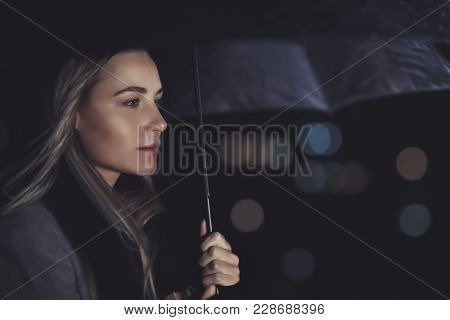 Portrait of a beautiful authentic woman standing under umbrella in rainy night, conceptual photo of loneliness and sadness