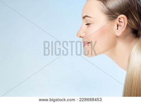 Closeup profile portrait of a nice blond girl with closed eyes isolated on blue background, conceptual photo of purity and beauty care with copy space