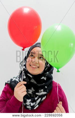 Happy muslim girl holding balloons