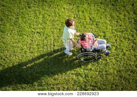 Elderly woman in wheelchair top view on grass with nurse taking care of her