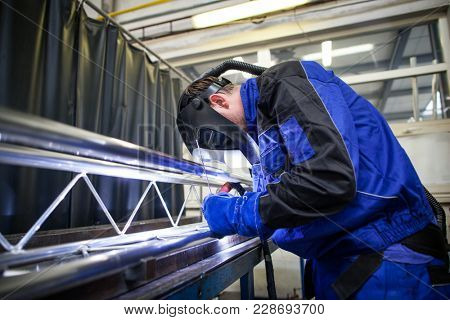Industrial workers welding metal with many sharp sparks, Welder working a welding metal with protective mask and sparks