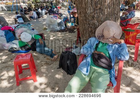 Bali, Indonesia - August 24, 2016: Unidentified balinese sarong vendors having rest in the shadow on the beach.