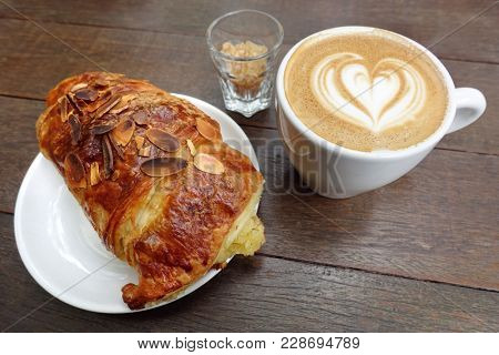 Perfect breakfast combination: cup of cappuccino and fresh baked almond croissant.