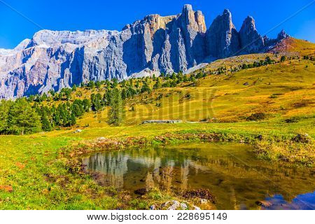 The majestic white and gray rocks are beautifully reflected in the puddle. Southern Limestone Alps. The most beautiful route in the Italian Dolomites. The concept of active and car tourism