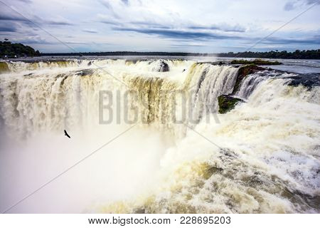 Grandiose waterfalls Iguazu in the rainy season - the Devil's throat. A spectacular journey to the grandiose exotic waterfalls on the Parana River. Concept of active and photographic tourism