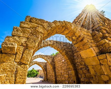 Dazzling spring sun illuminates the ancient Mediterranean port. The remains of the covered arcades in Caesarea. Israel. Concept of phototourism and historical tourism