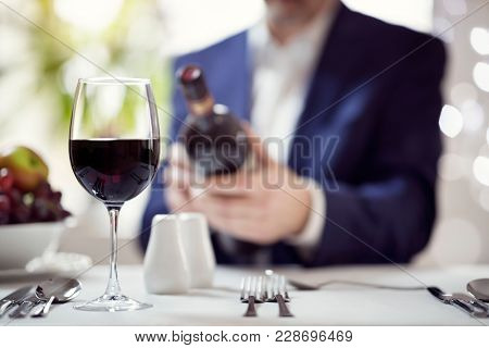 Businessman reading red wine bottle label in restaurant concept for business lunch or dinner meeting