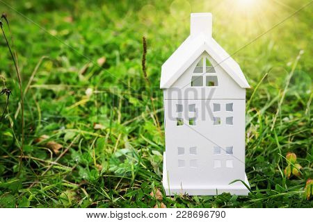 White House Layout On Green Grass. Small House On A Green Background Of Grass. Home Concept