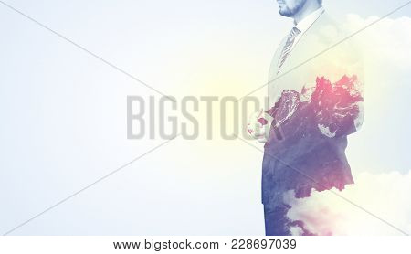 Businessman standing and thinking with snowy mountain graphic