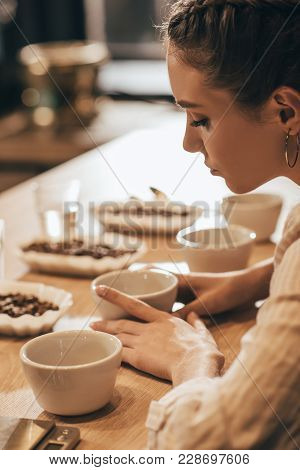 Side View Of Young Woman Testing Coffee Beans In Coffee Shop