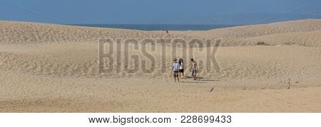 PRAIA DA BORDEIRA, PORTUGAL - AUGUST 20, 2017: People at the dunes of the famous beach of Praia da Bordeira. This beach is a part of famous tourist region of Algarve.