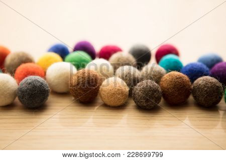 Warm colored dyed lambs wool balls, or felt spheres, in warm light. For something diverse. poster